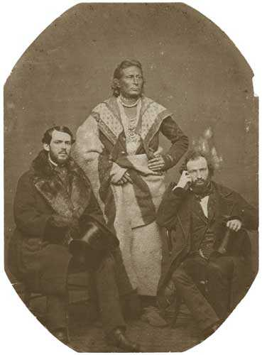 Black and white photo print of the Ho-Chunk (Winnebago) leader Baptiste Lasallier (center) with Indian Agent Charles H. Mix (right) and an Indian supply merchant from New York (left), 1857.