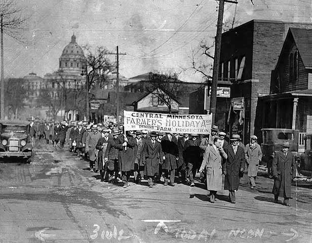 Photograph of marchers on a St. Paul street under a Farmers' Holiday sign