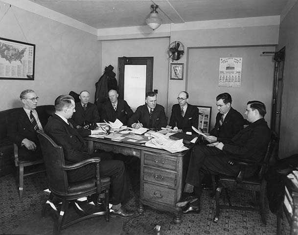 photograph of a group of men gathered around a desk in the State Office Building