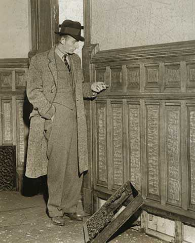 Black and white photograph of Richard R. Sackett, in charge of a historical records survey crew salvaging old documents at the second state capitol prior to demolition, inspects oak paneling, 1937. Photographed by the Minneapolis Tribune.