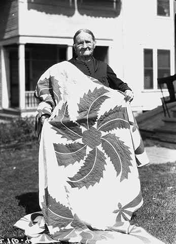 Black and white photograph of woman with prize-winning quilt, 1926.