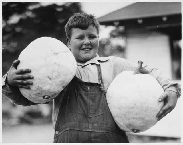 Black and white photograph of boy holding squash entered in the 1934 State Fair.