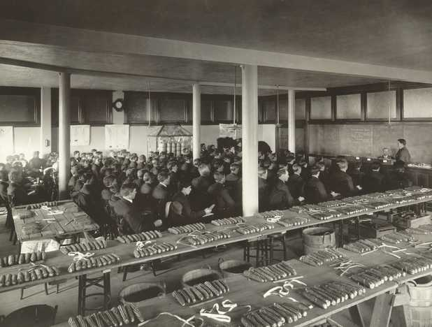 Black and white photograph of a class in corn judging, University of Minnesota, College of Agriculture, St. Paul, ca. 1910.