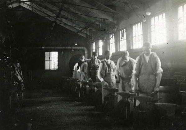 Black and white photograph of an Agriculture Extension, Short Course in Blacksmithing; men at the forges, 1908.