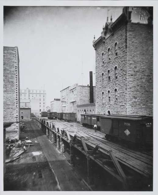 Black and white photograph of riverfront flour mills before the 1878 explosion.