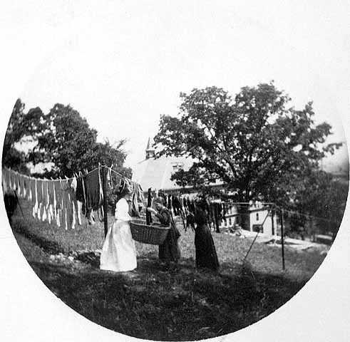 """Black and white photograph entitled """"Hanging up the clothes"""" at the James J. Hill House, 240 Summit, St. Paul, c.1900."""