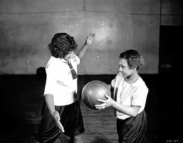 Black and white photograph of two girls playing basketball at Phyllis Wheatley House, ca. 1925.
