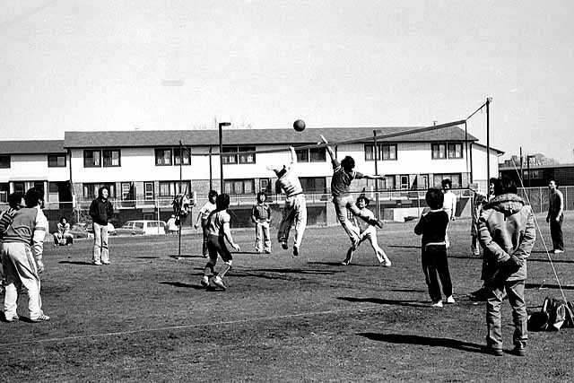 Hmong young people playing volleyball on the playground at Western and I-94, St. Paul, ca. 1980s. Photo by Michael Kieger.