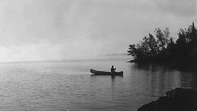 Black and white image of an individual canoeing on Lake Vermilion, 1935.