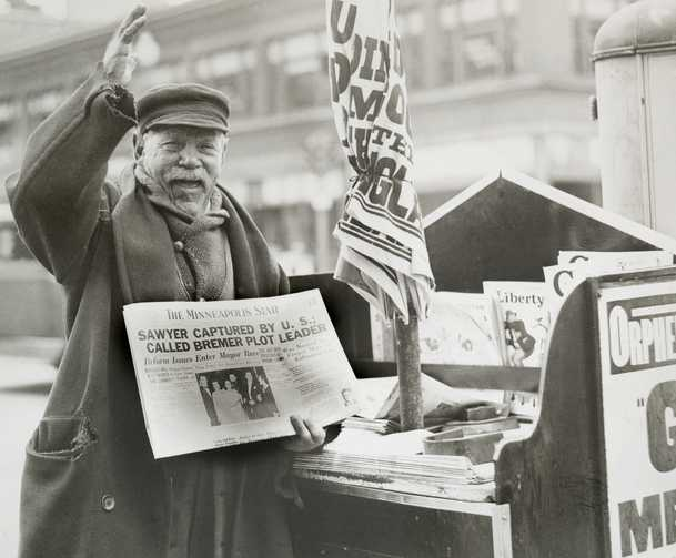 Black and white photograph of a man selling a newspaper with headline related to Bremer kidnapping, 1935.