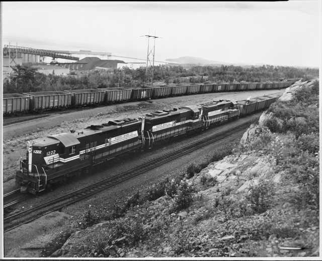 First Train of Taconite to Silver Bay, Minnesota, 1955. The first train of taconite from Reserve Mining Company's Peter Mitchell Pit was shipped to the concentration facilities in Silver Bay in 1955.