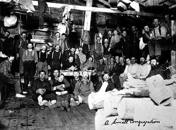 Photograph of a small congregation of lumberjacks assembled inside a bunkhouse to hear sky pilot Frank Higgins preach c.1910.