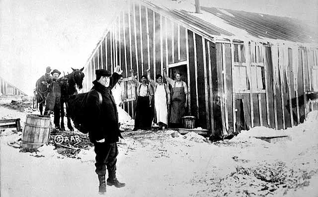 Photograph of men waving to Frank Higgins, the lumberjack sky pilot, outside a lumber camp c.1910.