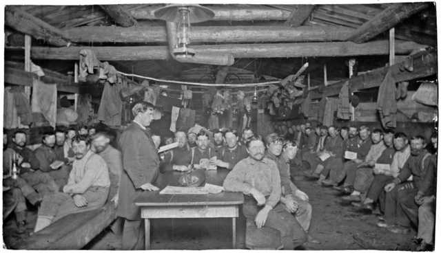 Photograph of Frank Higgins preaching to a group of lumberjacks in a bunkhouse c.1910.