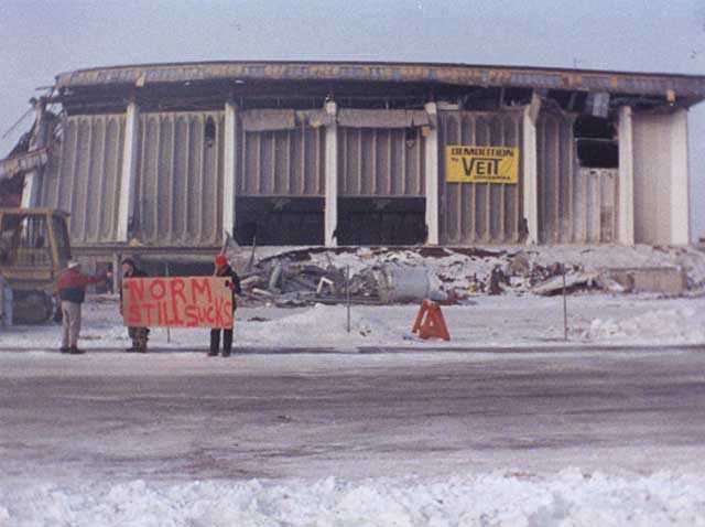 """Demolition of the Met Center (Metropolitan Sports Center) in Bloomington, 1994. The stadium was demolished after the North Stars hockey team left Minnesota. A common refrain among North Stars fans, who blamed owner Norm Green for abandoning the state, was """"Norm sucks."""""""
