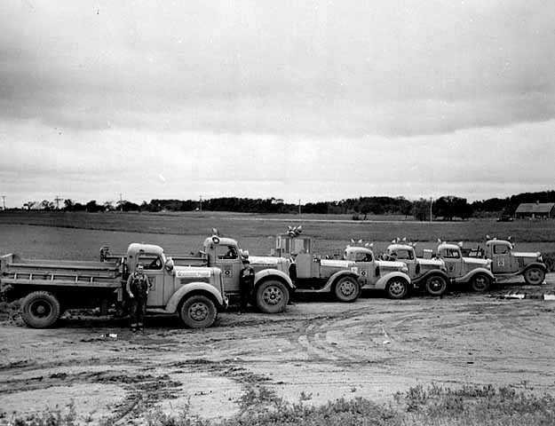 Black and white photograph of highway trucks delivering grasshopper poison to farmers, 1938.