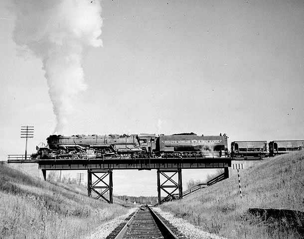 Black and white photograph of a Duluth, Missabe and Iron Range train on railroad bridge west of Two Harbors, ca. 1940.