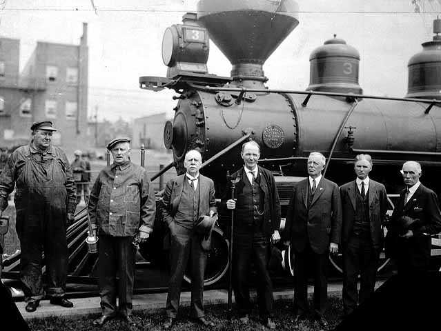 Black and white photograph of the first locomotive to bring iron ore to the Duluth docks with dignitaries and crew members, 1934.