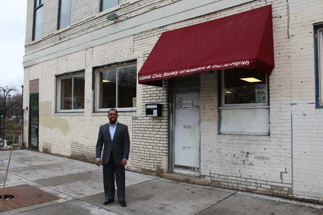 Color image of Wali Dirie, executive director of the Islamic Civic Society of America and Dar Al-Hijrah Mosque, stands outside their new entrance at 504 Cedar Avenue, 2015.