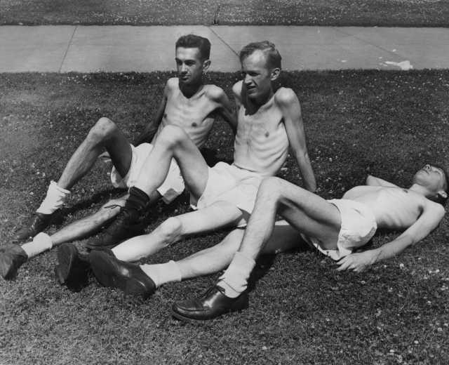 Black and white photograph of volunteers Gerald Wilsnack, Marshall Sutton, and Jasper Garner relax in the sun between their daily routine, c.1944.