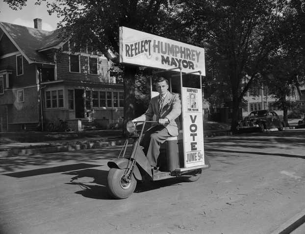 """Black and white photograph of a """"Hubert Humphrey for mayor"""" campaign worker rides his Cushman scooter before the Minneapolis mayoral election, 1947."""