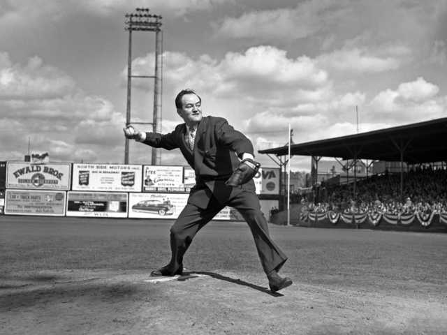 Black and white photograph of Minneapolis Mayor Hubert Humphrey throws out the first pitch of a baseball game played by the Minneapolis Millers at Nicollet Park in Minneapolis on April 27, 1948.