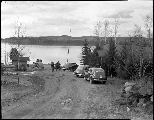 A view of cars, visitors, and Gunflint Lake at Gunflint Lodge. Photograph by Kenneth Melvin Wright, ca. 1950.