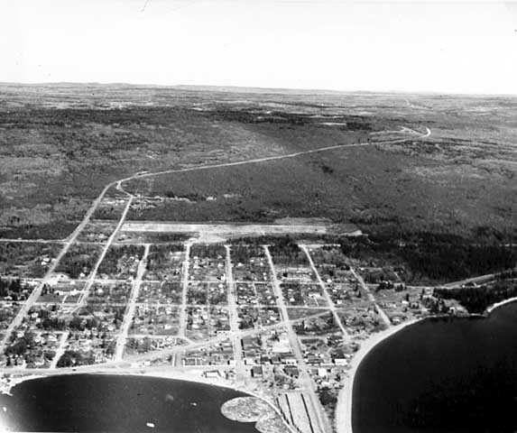 An aerial view of Grand Marais, ca. 1955. The diagonal white line that can be seen in the background is the Gunflint Trail.