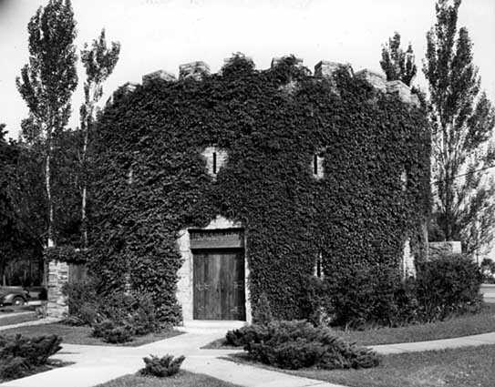 Black and white photograph of the he Round Tower covered in vegetation, c.1942. Photographed by Norton and Peel.