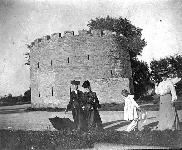 Black and white photograph of women with parasols by round tower, c.1900.