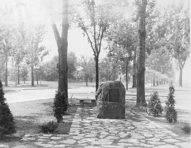Black and white photograph of a monument erected to the memory of Colonel Josiah Snelling in front of the Fort Snelling Memorial Chapel, 1929.