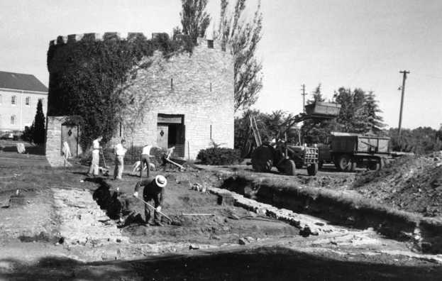 Black and white photograph of an archaeological crew and mechanical equipment near the Round Tower, 1958.