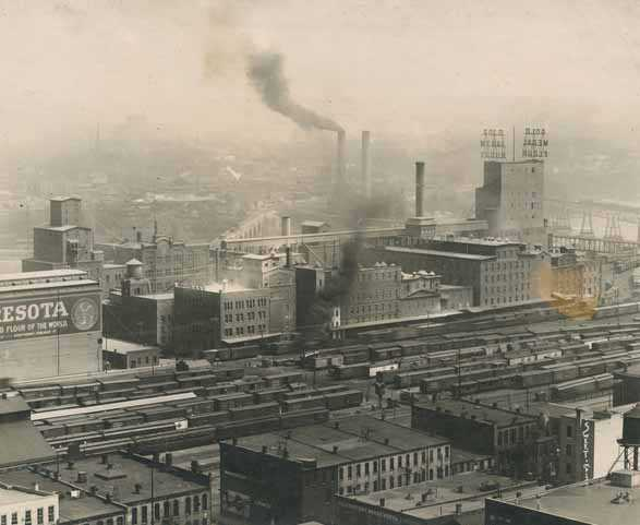 Black and white photograph of the the West Side Milling District of Minneapolis from the courthouse showing the extensive rail yards required for the shipping of grain and flour, ca. 1912. Photograph by Sweet.