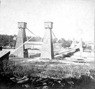 Black and white photograph of the Hennepin Avenue Bridge looking toward Nicollet Island, c.1865.