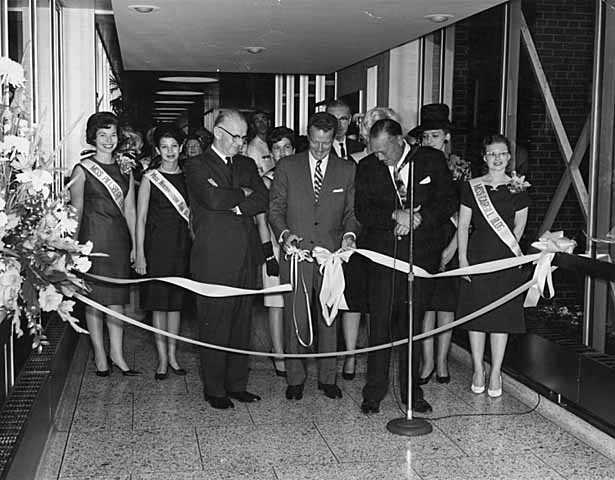 Black and white photograph of he opening of the first Minneapolis skyway, connecting the Northstar Center and the Northwestern National Bank; Leslie Park is at left, 1962.