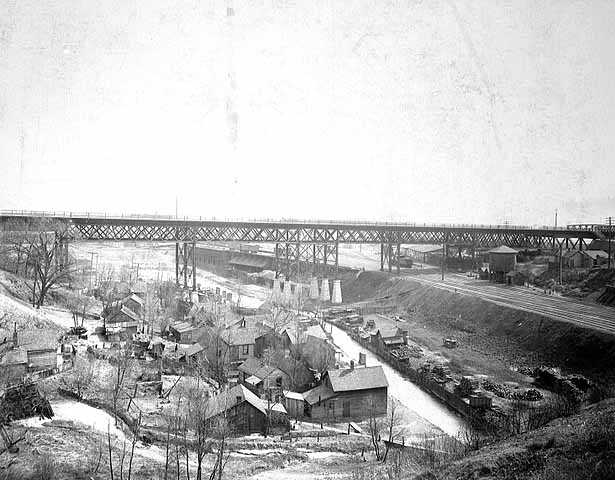 Black and white photograph of Swede Hollow with the Sixth Street Bridge in the background, c.1900.
