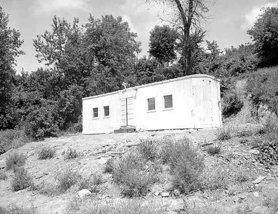 Black and white photograph of boxcar chapel in Swede Hollow, 1949.