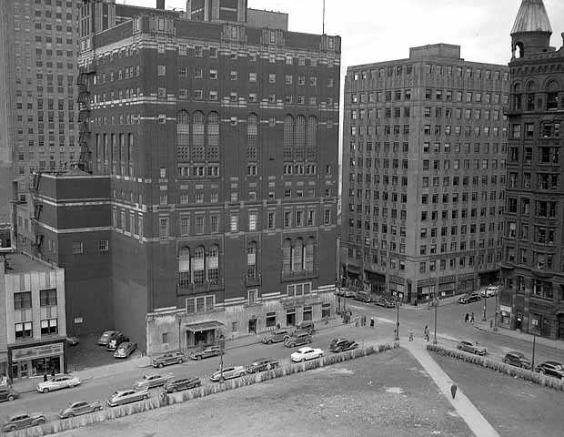 Black and white photograph of the St. Paul Athletic Club and surrounding buildings. View of the intersection of Fourth Street East and Cedar Avenue, St. Paul. The St. Paul Athletic Club is at center left.