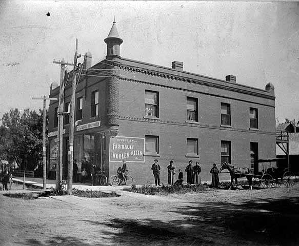 Black and white image of the Office of Faribault Woolen Mills, founder Carl H. Klemer standing to right of bicycle, 1897.