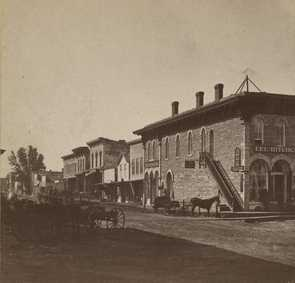Black and white photograph of Division Street, Northfield 1870. The First National Bank is the first door to the left of the staircase. Photographed by Sumner's Gallery.