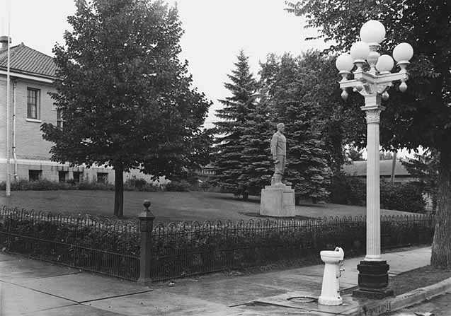 Black and white photograph of the statue of Leonidas Merritt in front of the public library in the town of Mountain Iron, 1940.