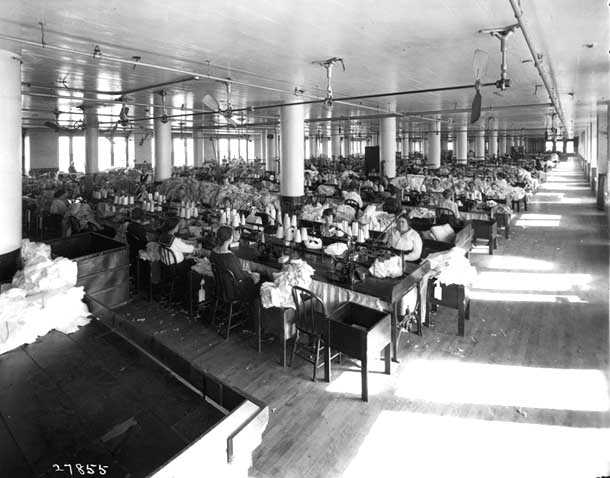 photograph of a room full of women at sewing machines