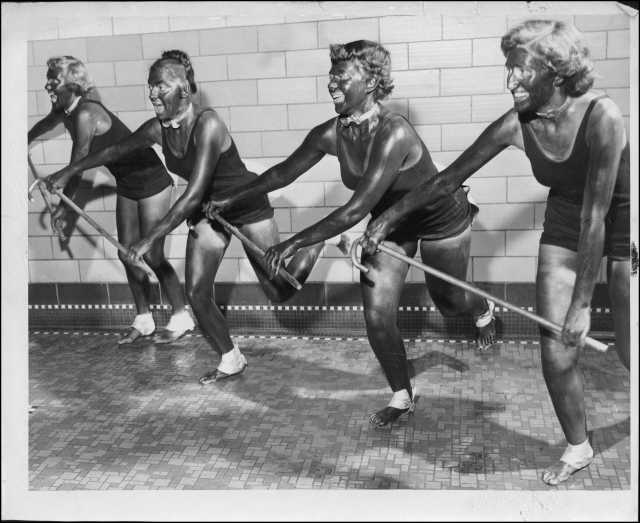"""University of Minnesota students, and members of the campus Aquatic League, practice a dance number in blackface for the comic water ballet to be performed in the Cooke Hall exhibition pool on Friday night. L to R: Susan Fredrickson of Santa Cruz, California; Trudy Schlek of Milwaukee, Wisconsin; Kit Thiele of Madison, Minnesota; and Gerrie Ghent of St. Paul, rehearse a """"Licorice Lindy"""" dance number with canes in Cooke Hall. Originally published in the Minneapolis Tribune, April 14, 1950."""