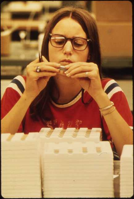 3M employee at work in New Ulm, 1974. 3M had (and has, as of 2019) a factory in New Ulm that built electrical parts. Public domain.