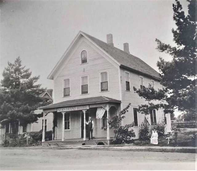 Three unidentified people in front of the Nerstrand Hotel with American flags on display, ca. 1890. Nerstrand city records, Nerstrand City Hall.