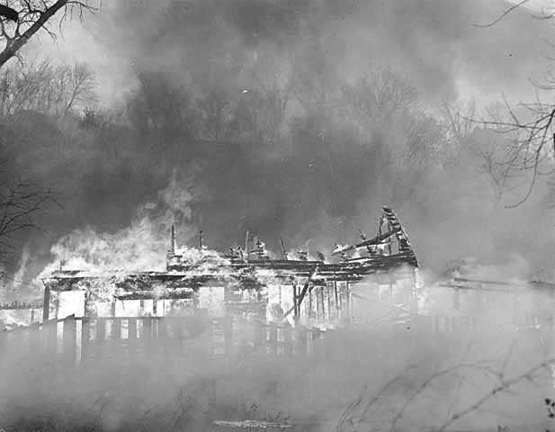 Black and white photograph of the burning of Swede Hollow, St. Paul, 1956.