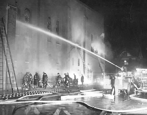 Black and white photograph of firefighters fighting the blaze at St. Paul's Temple of Aaron in 1952.