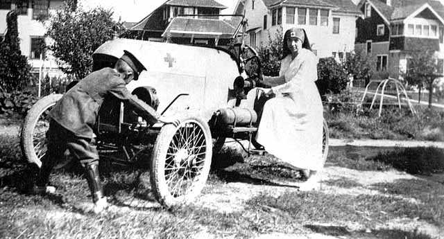 Black and white photograph of a Red Cross nurse, and likely Motor Corps officer, 1918. The car has the Red Cross symbol on the hood and was likely part of the Minnesota Motor Corps.