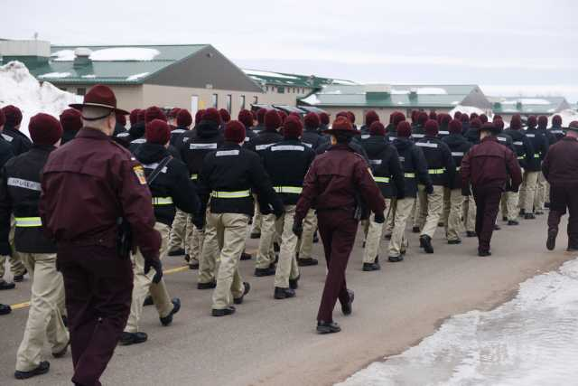 Color image of cadre and candidates of the Minnesota State Patrol's Trooper Academy march between classes at Camp Ripley, February 2016.
