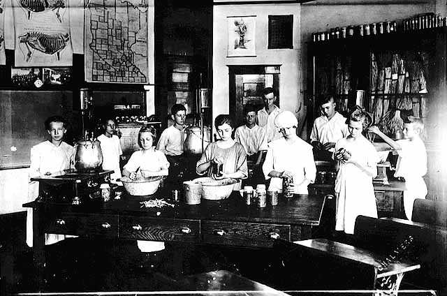 Black and white photograph of members of the Boys and Girls Club participating in a canning demonstration, 1920.